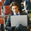 Stock Photo: Businessman sitting in the airport b