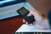 Mão e telefone móvel — Fotografia Stock