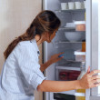 Woman looking in the fridge — Stock fotografie