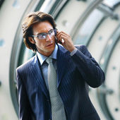 Talking on mobile phone in office lobby — Stock Photo