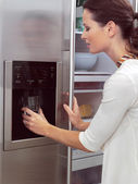 Woman in front of the fridge aa — Stock Photo