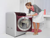 Young woman doing laundry — Stock Photo