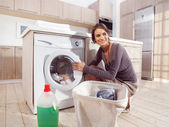 Woman putting cloth into washing machine — Stock Photo