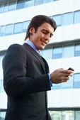 Un uomo d'affari utilizzando il telefono cellulare b — Foto Stock