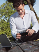 A smiling man with laptop — Stock Photo