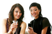 Girls checking out their new mobilephone — Stock Photo