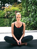 Sporty girl sitting in yoga pose — Stock fotografie