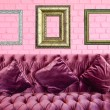 Vintage violet sofa and vintage picture frame on pink brick wall — Stock Photo
