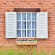 Beautiful white wooden window on old brick wall — Stock Photo