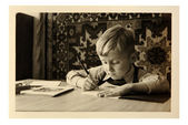 Old photo: boy writes in notebook — 图库照片