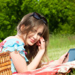 Beautiful woman enjoys the tablet at a picnic — Stock Photo