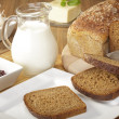 Breakfast with wholemeal bread, jam and milk or orange juice — Stock Photo