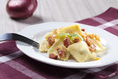 Portion of ravioli with onion and bacon — Stock Photo