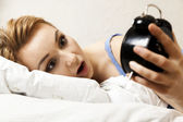 Beautiful young woman sleeping on bed with alarm clock  — Stock Photo