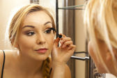 Beautiful woman doing makeup on her face — Stock Photo