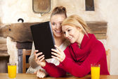 Two beautiful women work on the tablet — Stock Photo