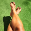 图库照片: Relaxed feet of womlaying in grass