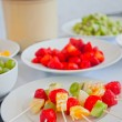 Kebabs with pieces of strawberry, mandarin and kiwi , fruit skewers  — Photo