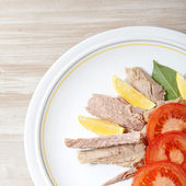 Canned tuna chunks with tomato and lemon on wooden table — Stock Photo