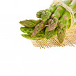 Fresh green asparagus bunchon a piece of canvas isolated on white background — Stock Photo #27605771
