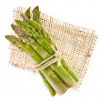 Fresh green asparagus bunchon a piece of canvas isolated on white background — Stock Photo #27605783