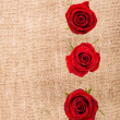 Three red roses against a canvas bag — Stock Photo