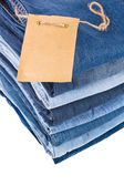 Lot of different blue jeans in the stack close-up isolated on white background — Stock Photo