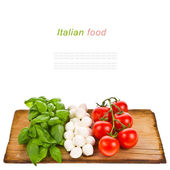 Ripe tomatoes and mozzarella balls garnished with basil — Stock Photo
