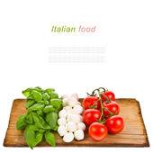 Ripe tomatoes and mozzarella balls garnished with basil — Stock Photo