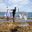 Theme wedding - the bride and groom on the sea holding hands, in the foreground champagne glasses — Stok fotoğraf