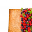 Blueberries, strawberry, raspberries and cherry on a wooden tray isolated on white background — Stock Photo #28343769