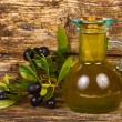 Olive oil in a small glass bottle with olive tree branches and old boards — Foto de Stock