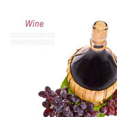 Red wine in a pot-bellied bottle with a wicker basket and grapes with drops of water isolated on white background — Stock Photo