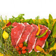 Fresh meat - fresh steaks on a yellow mat, fresh herbs and vegetables isolated on white background — Stock Photo #30084767