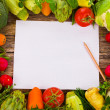 Topic cooking - lots of different vegetables and herbs on an old wooden and paper notebook for recipes board as a background — Stock Photo