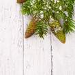 Theme New Year holidays and Christmas Green spruce branches with cones on a white background painted old wood planks as background — Stock fotografie