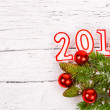 Branch of Christmas tree with numbers in 2014 sprinkled with snow and red Christmas balls on a white background painted old wood planks as background, concept of new year — Stock Photo