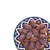 Large dry dates on a plate isolated on white background — Stock Photo