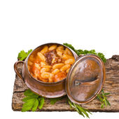 Traditional spanish beans stew native from Asturias Region in an old copper pot - Fabada Asturiana isolated on white background — Stock Photo