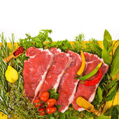 Fresh meat - fresh steaks on a yellow mat, fresh herbs and vegetables isolated on white background — Stock Photo