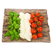 Ripe tomatoes and mozzarella balls garnished with basil Italian food ingredients forming the italian flag on the old board isolated on white background — Stock Photo