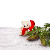 Theme New Year holidays and Christmas Green spruce branches with cones and teddy bear on a white background painted old wood planks as background — Stock Photo