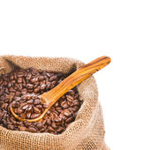 Coffee beans in canvas sack , with a wooden spoon — Stock Photo