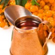 Small brass pitcher with sea buckthorn oil — Stock Photo #40294405