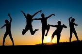 Šťastné děti siluety skákání na pláži — Stock fotografie