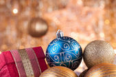Gold and blue christmas baubles and red box — Stock Photo