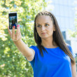 Beautiful young woman taking photo of herself with her mobile ph — Stok fotoğraf