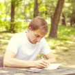 Young Man Writing Something Outdoors — Stock Photo
