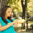 Beautiful girl checking the time outdoors — Stock Photo