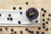 Blueberry smoothie on wooden background — Stock Photo